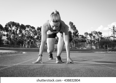 Black and white image of a female sprinter athlete getting ready to start a race on a tartan racetrack with dramatic lighting late in the afternoon, just before dusk