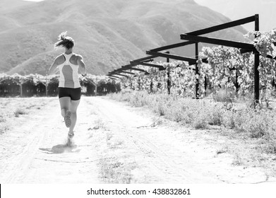 Black and white image of a Female triathlete running on a trail on a bright sunny day in the vineyards of the Western Cape of South Africa