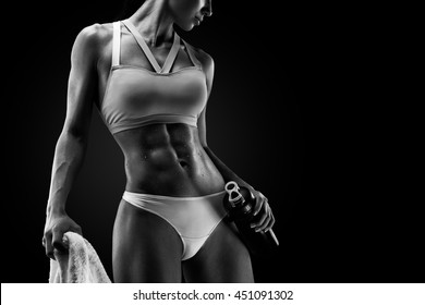 Black and white Image of fitness woman in sports clothing looking down. Young female model with muscular body. Horizontal studio shot with copy space on black background.
