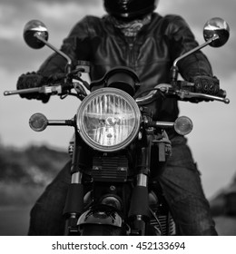 Black and white image of the front of a motorbike showing headlamp and mirrors.  Which adult male in leathers.