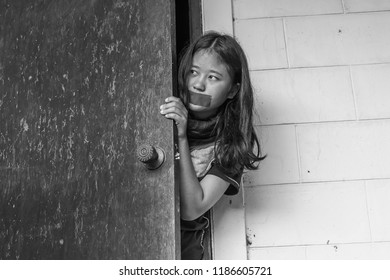 Black and white image of a girl open the door for run away from criminal.
