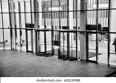 Black and white image of a group of revolving doors on a London office building.