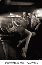 Black white image of a handsome couple hugging in a luxury limousine