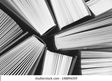 A black and white image of hardback books or text books from above. Books and reading are essential for self improvement, gaining knowledge and success in our careers, business and personal lives