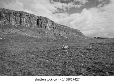 Black and white image of high cliff on Malham Moor under a cloudy sky.