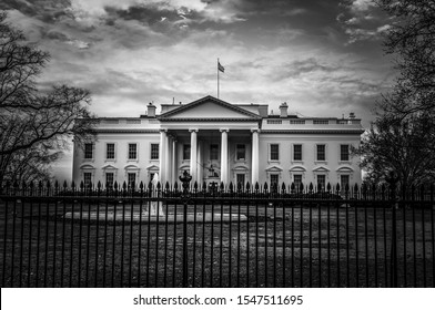 Black and white image of the White House presidential residence and office in Washington DC with iron fence and fountain in front and cloudy sky in background