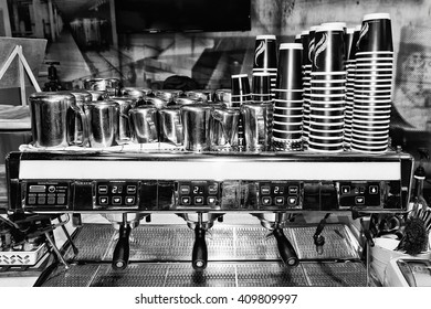 Black white image of industrial large scale barista coffee machine in a cafe ready to serve customers with piles of cups and milk pots around counter.