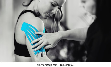 Black and white image of kinesiology taping treatment with blue tape on female patient injured arm. Sports injury kinesio treatment.