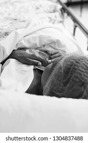 A black and white image of a black lady lying in a hospital bed in a theatre waiting are, waiting for her cesarean section