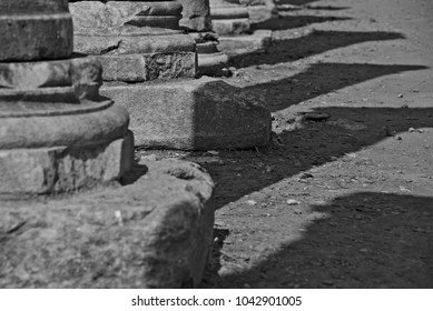 Black and white image of a line of column bases with nice shadows on the ground.