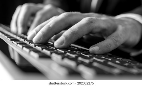 Black and white image of male hands typing on  computer keyboard.