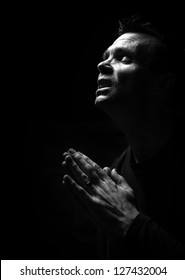 A black and white image of a man kneeling down praying to God.