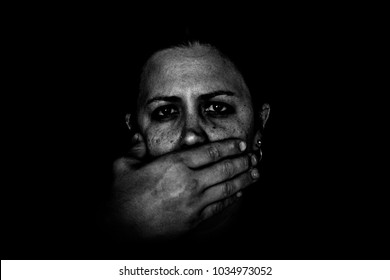 Black and white image of man's hand covering woman's mouth on black background. Domestic violence. Fear. No Voice. Removal of free speech