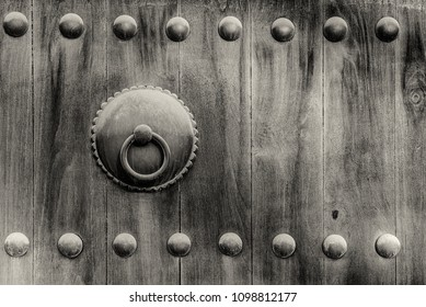 A black and white image of a metal door knocker on the wooden door of a traditional arabian house.