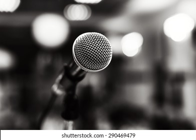 Black and white image of microphone with lights in background