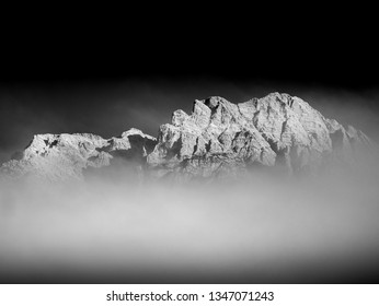 Black and white image of mountain peak with clouds in the alps in austria europe