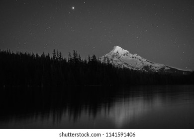 A black and white image of Mt Hood during the start of the stars coming out and Jupiter shining above the horizon.