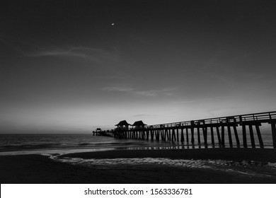 Black and white image of the Naples Pier in downtown Naples, Florida, silhouetted against a recently set sun, with the crescent moon shining above.