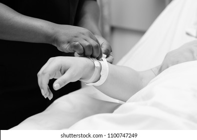 A black and white image of a nurse assisting a pregnant lady with her admission bracelets, where the close up is on the nurse and patients hand.
