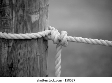Black and white image of a nylon rope tied to a pole