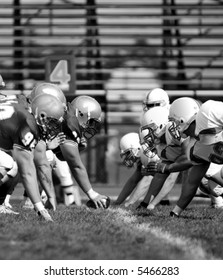Black and white image of offensive and defensive linemen going head to head.