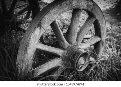 A black and white image of an old cartwheel.  The cartwheel is a traditionally made construction with wooden spokes and steel band tyre.