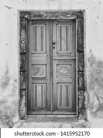 Black and white image of an old doorway in Santorini, Greece.  Film grain/analog filters.