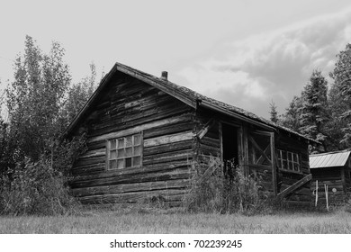 A black and white image of an old log cabin.