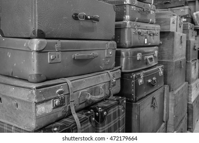 Black and white image of old pile of travelling leather suitcases