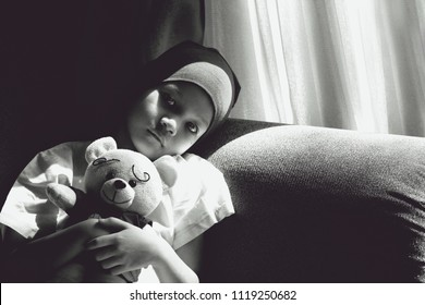 Black and white image of Patient kid lie down on couch with doll.Girl cover her head with headscarf.Kid look sad,tired and sick.Concept of   childhood cancer awareness.Selective focus.