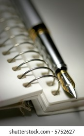 Black and white image of Pen and spiral bound book