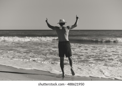 Black and white image of person walking on summer beach outdoors background. Rear view of male in hat going swimming