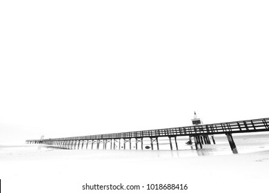 Black and white image of a pier photographed by the foreshore during low tide