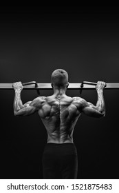 Black and white image of power muscular bodybuilder guy doing pullups in gym. Fitness man pumping up lats muscles. Fitness and bodybuilding training health lifestyle concept Fitness man rear view.