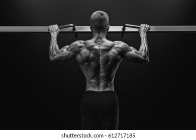 Black and white image of power muscular bodybuilder guy doing pullups in gym. Fitness man pumping up lats muscles. Fitness and bodybuilding training health lifestyle concept