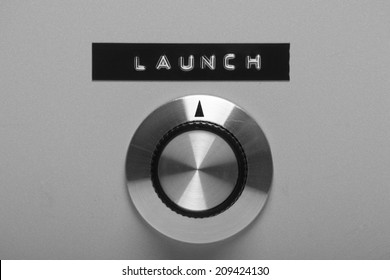 Black and white image of a retro style control switch on a metal panel, pointing at a printed label with the word Launch