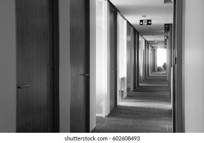 Black and white image of Rolls of empty bright office hallway at dawn