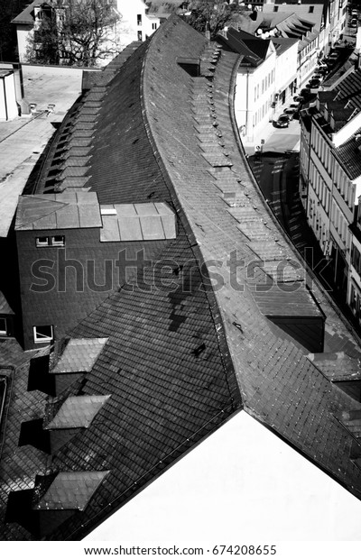 Black and white image of the roof of a long building with an S-curved ridge line