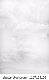 black and white image of seaside ocean mountains and sky and clouds - abstract background