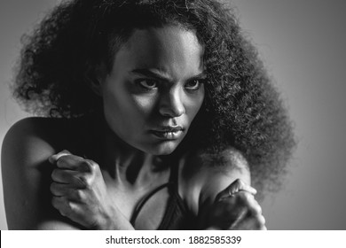 Black and white image. Self-defense, fearful African American girl standing covered with hands in black bare shoulder top isolated on grey background. Human emotions, facial expression concept.
