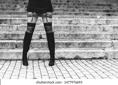 Black and white image of a sexy woman in long black boots wearing stockings and suspenders standing in the street in front of steps in a low angle view of her legs
