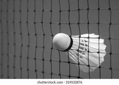 Black and white image of shuttlecocks struck on the net in badminton court for sport background