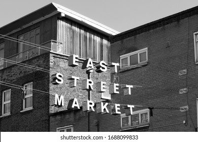 A black and white image of the sign hanging above the East Street Market, a street market in Walworth, South London, which is also known as'The Lane', or 'East Lane'.  Image has copy space.