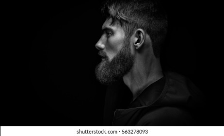 Black and white image of single standing in profile young handsome serious bearded man in black hoodie over black background with copy space.