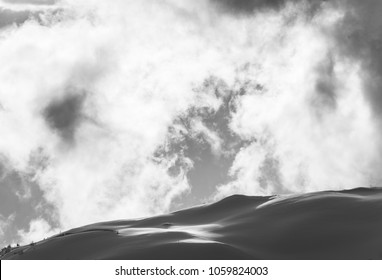 black and white image of snow covered hills with illuminated clouds in the swiss alps