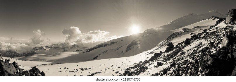 Black and white image of snow covered mountain landscape. The Sun peaks out behind the mountains. Taken on Mt Elbrus, Russia