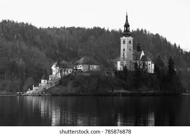 Black and white image of St. Mary Church of the Assumption on the small island in the middle of the lake; Bled, Slovenia.