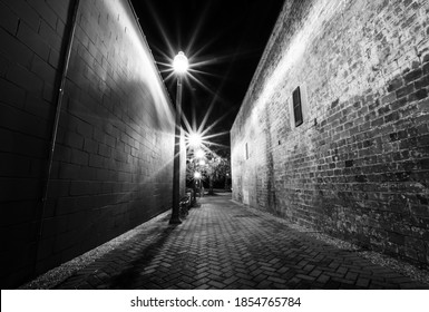 Black and white image of street lamps in an alleyway lit up at night.