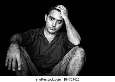 Black and white image of a stressed and worried young man sitting on the floor isolated on a black background