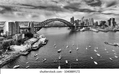 Black white image of Sydney city CBD landmarks across Harbour along Sydney Harbour bridge with contrast atmospheric clouds over high-rise towers.